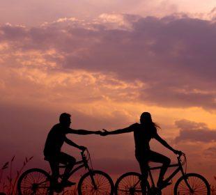 Couple à vélo coucher de soleil